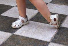 Pés das meninas que vestem sandálias Imagens de Stock