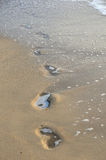 Pés das pegadas na praia da areia Fotografia de Stock Royalty Free