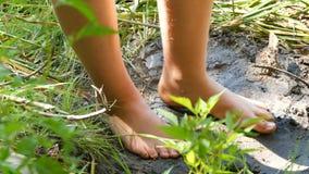 Pés de adolescente no suporte no banco de um rio selvagem na lama e na grama naturais filme