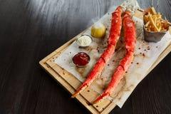 Pés de caranguejo cozinhados do rei com molhos e batatas fritas fotos de stock