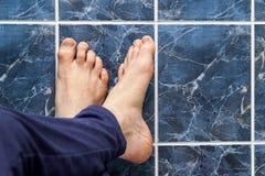 Pés de cruzamento do homem novo em telhas quadradas Veias nos pés visíveis Fotografia de Stock Royalty Free