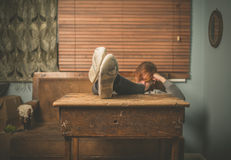 Pés de descanso da mulher na tabela Fotografia de Stock