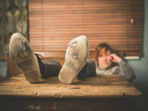 Pés de descanso da mulher na tabela Foto de Stock
