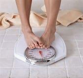 Pés de dieta do ` s da mulher que cobrem acima a leitura de escala Imagem de Stock