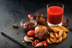 Pés de frango frito com batatas, vegetais, tomates, pimenta, molho e um vidro do suco de tomate em um fundo preto Fotografia de Stock