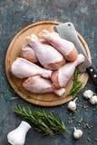 Pés de galinha crus crus, pilões na placa de madeira, carne com os ingredientes para cozinhar Fotos de Stock Royalty Free
