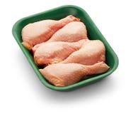 Pés de galinha crus em uma bandeja verde sobre o fundo branco Fotos de Stock