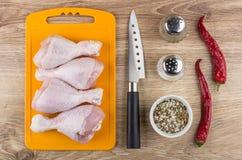 Pés de galinha crus na placa de corte, no sal, na pimenta e na faca Imagens de Stock Royalty Free
