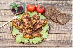 Pés de galinha e folhas grelhados da alface na placa de desbastamento de madeira com molho e pão imagem de stock royalty free