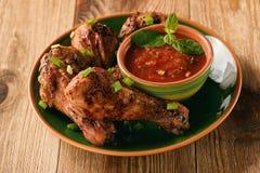 Pés de galinha e molho de tomate Roasted no fundo de madeira Imagem de Stock