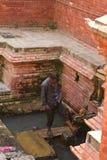 Pés de lavagem do homem em Kathmandu, Nepal fotografia de stock
