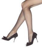 Pés de mulher nova em sapatas pretas high-heeled Imagem de Stock