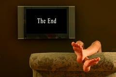 Pés de reclinação da criança que prestam atenção acima ao fim de um filme foto de stock