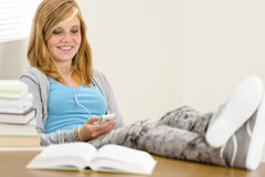 Pés de relaxamento de sorriso do adolescente do estudante na tabela Imagens de Stock