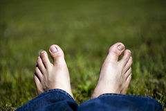 Pés de relaxamento na grama Imagens de Stock