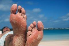 Pés de relaxamento na praia   Imagens de Stock