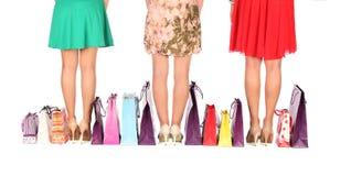 Pés de três amigas glamoroso com sacos de papel Fotografia de Stock Royalty Free