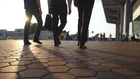Pés de três homens de negócios que andam perto do aeroporto com o alargamento do sol no fundo Os homens de negócio vão ao termina filme