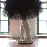 Pés de um close up da bailarina Os pés de uma bailarina no pointe velho Bailarina do ensaio no salão Luz do contorno da janela fotografia de stock