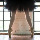Pés de um close up da bailarina Os pés de uma bailarina no pointe velho Bailarina do ensaio no salão Luz do contorno da janela imagem de stock