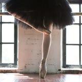 Pés de um close up da bailarina Os pés de uma bailarina no pointe velho Bailarina do ensaio no salão Luz do contorno da janela imagens de stock