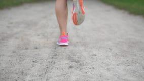 Pés de um corredor da mulher que corre ao longo da estrada em um dia de verão, close-up vídeos de arquivo