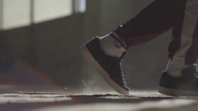 Pés de um dançarino profissional nas sapatilhas que dançam em um assoalho concreto empoeirado em uma casa abandonada video estoque