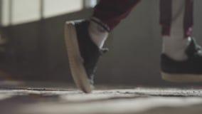 Pés de um dançarino profissional nas sapatilhas que dançam em um assoalho concreto empoeirado em uma casa abandonada vídeos de arquivo