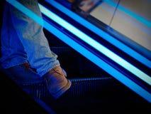 Pés de um homem em escadas moventes Foto de Stock