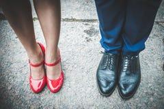 Pés de um homem em sapatas e em mulheres pretas em sapatas vermelhas Co romântico Fotos de Stock