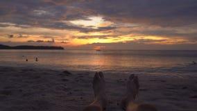 Pés de um homem em uma praia que olha um por do sol fantástico vídeos de arquivo