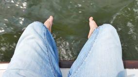 Pés de um homem que senta-se na curva do barco ou do iate filme