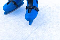 Pés de um skater de gelo em patins velhos do vintage Fundo skratched gelo imagem de stock