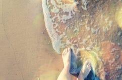 Pés de uma água tocante da jovem mulher foto de stock royalty free