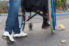 Pés de uma equipa de tratamento que empurra uma cadeira de rodas Imagem de Stock Royalty Free