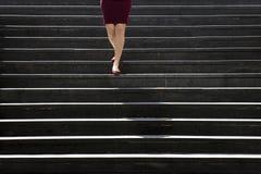 Pés de uma jovem mulher em sapatas e no vestido vermelhos que anda abaixo do st Fotos de Stock