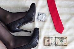 Pés de uma menina nos saltos, nos preservativos, no dinheiro e em uma fêmea do laço foto de stock