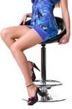 Pés de uma mulher bonita que senta-se em uma cadeira. imagens de stock
