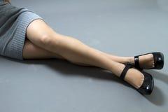 Pés de uma mulher em um vestido com sapatas pretas Imagens de Stock