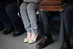 Pés de uma mulher nas calças de brim Imagens de Stock