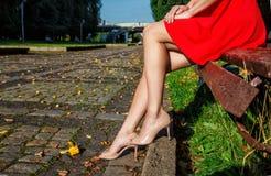 Pés de uma mulher que senta-se em um banco de parque foto de stock royalty free