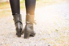 Pés de uma mulher que vestem o salto alto preto das botas Fotos de Stock
