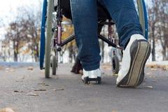 Pés de uma pessoa que empurra uma cadeira de rodas Fotos de Stock