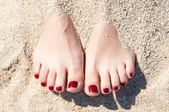 Pés de Womans na areia Imagem de Stock