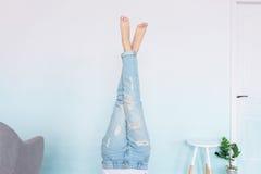 Pés de Women's na calças de ganga com pedicure branco em um fundo azul e branco do inclinação imagens de stock royalty free