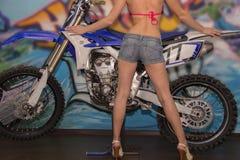 Pés delgados bonitos de uma moça no short das calças de brim em um azul Fotos de Stock Royalty Free