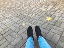 Pés delgados fêmeas nas calças de brim e botas, sapatas contra um fundo de pavimentos concretos da pedra cinzenta e das folhas am fotos de stock royalty free