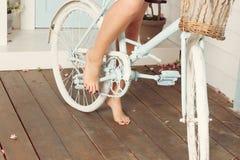 Pés desencapados da mulher perto da bicicleta azul Fotografia de Stock