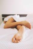 Pés desencapados de um sono da jovem mulher Imagem de Stock