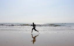 Pés desencapados do homem que corre na praia Fotografia de Stock